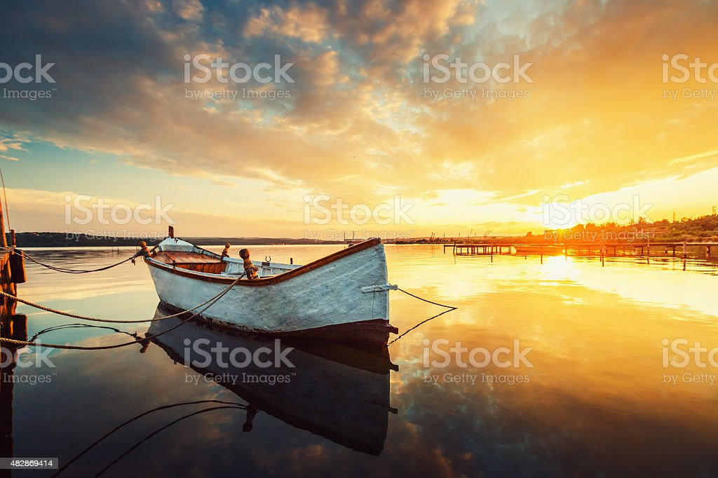 Beautiful sunset over calm lake and boat with water reflecting stock photo