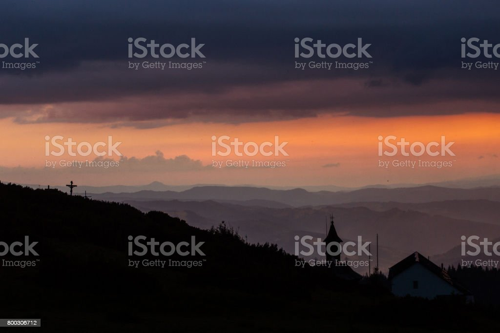 Beautiful sunset over mountains with storm clouds in background. Masivul Ceahlau, Romania. stock photo