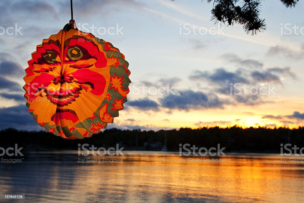 Beautiful sunset over water in Stockholm Arcipelago with paper lantern. royalty-free stock photo