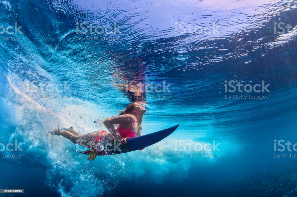 Young active girl wearing bikini in action - surfer with surf board...
