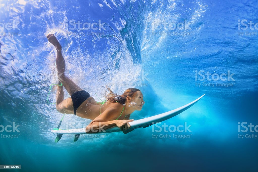 Young active girl in bikini in action - surfer with surf board dive...