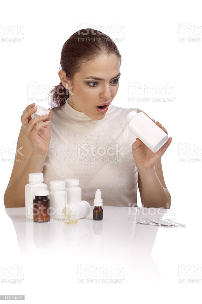 Beautiful surprised young woman looking into the pill bottle.XXXL royalty-free stock photo