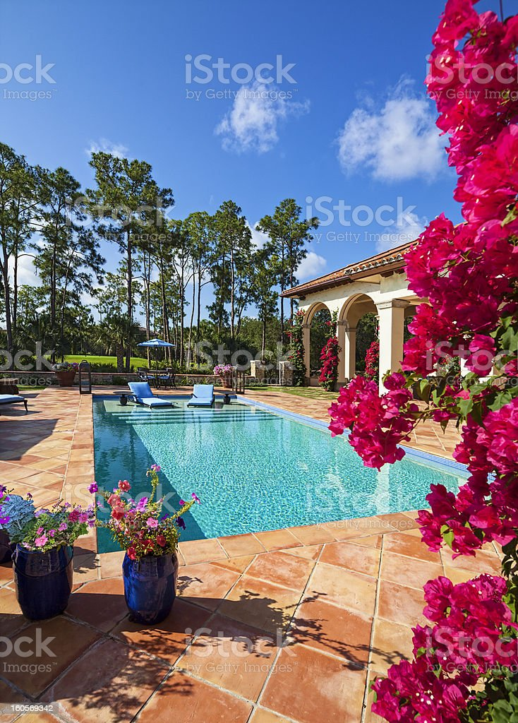 Beautiful Swimming Pool with Lounge Chairs in the Water royalty-free stock photo
