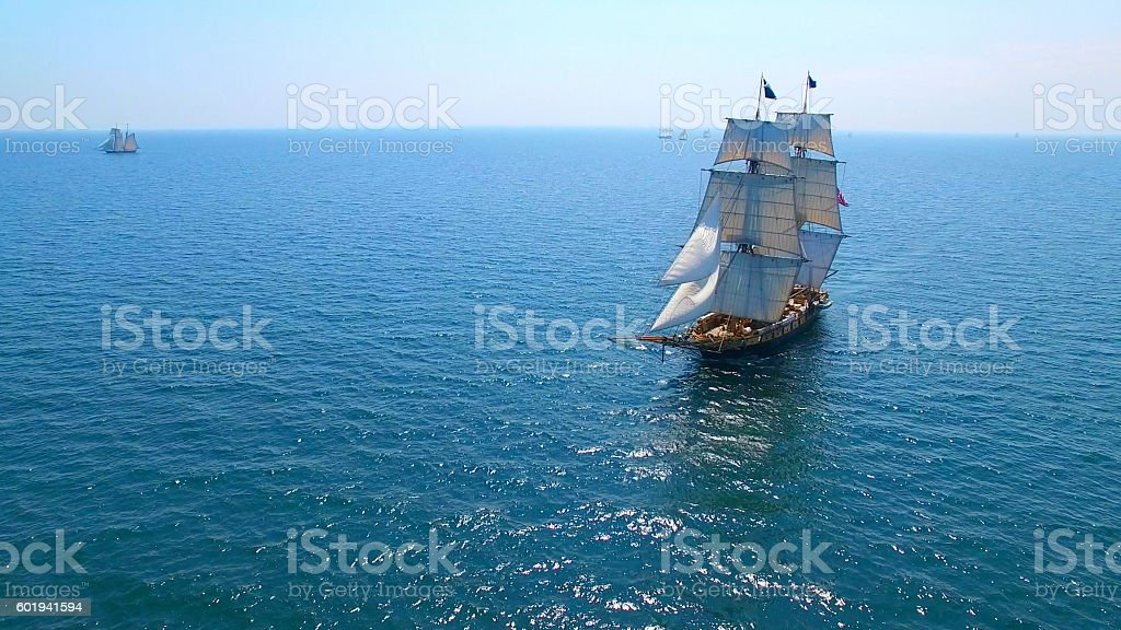 Beautiful tall ship sailing deep blue waters toward adventure stock photo