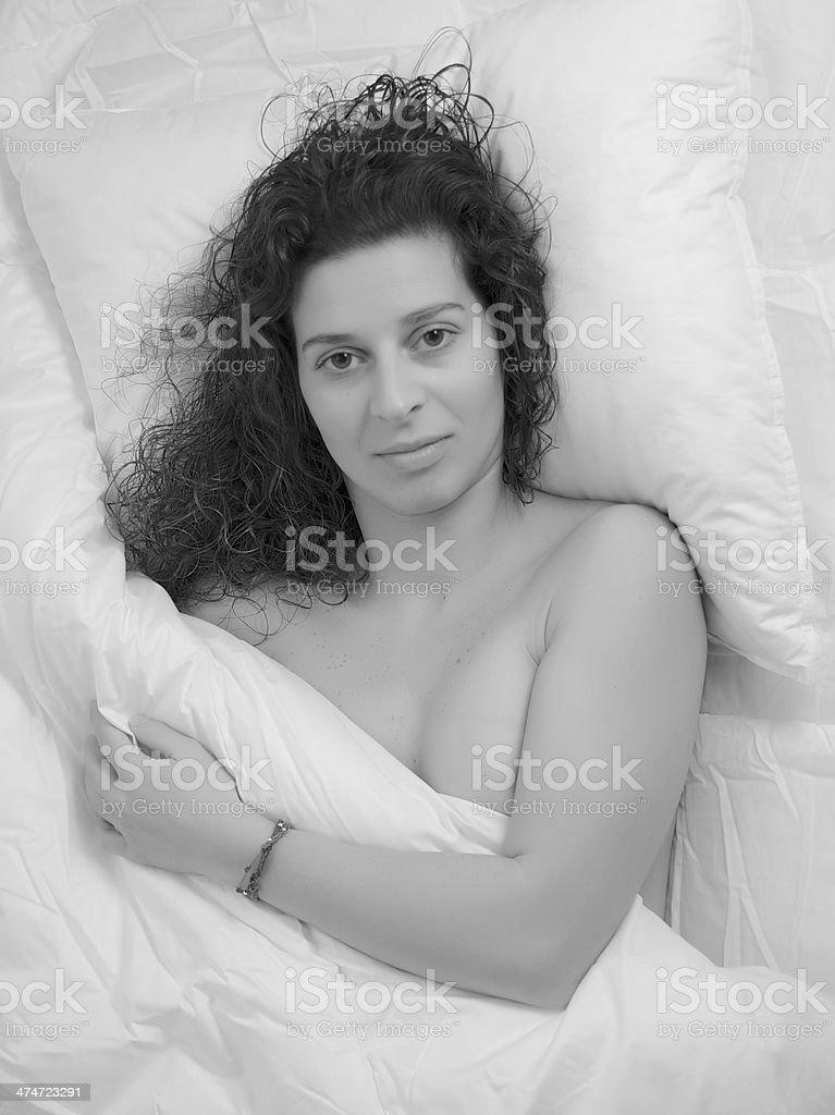 Beautiful tan woman modeling black lingerie on white sheets.