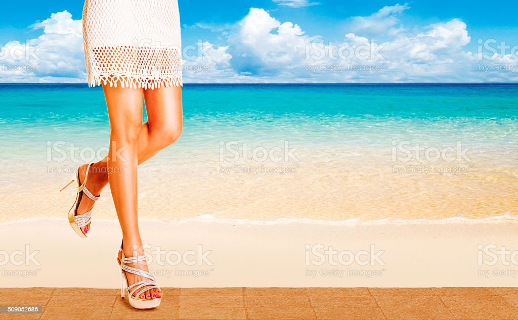 Beautiful tanned legs woman walking in the beach side. stock photo