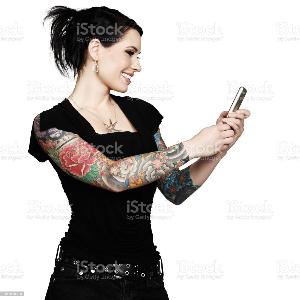 Beautiful tattooed woman smiles while using mobile phone. White background. royalty-free stock photo