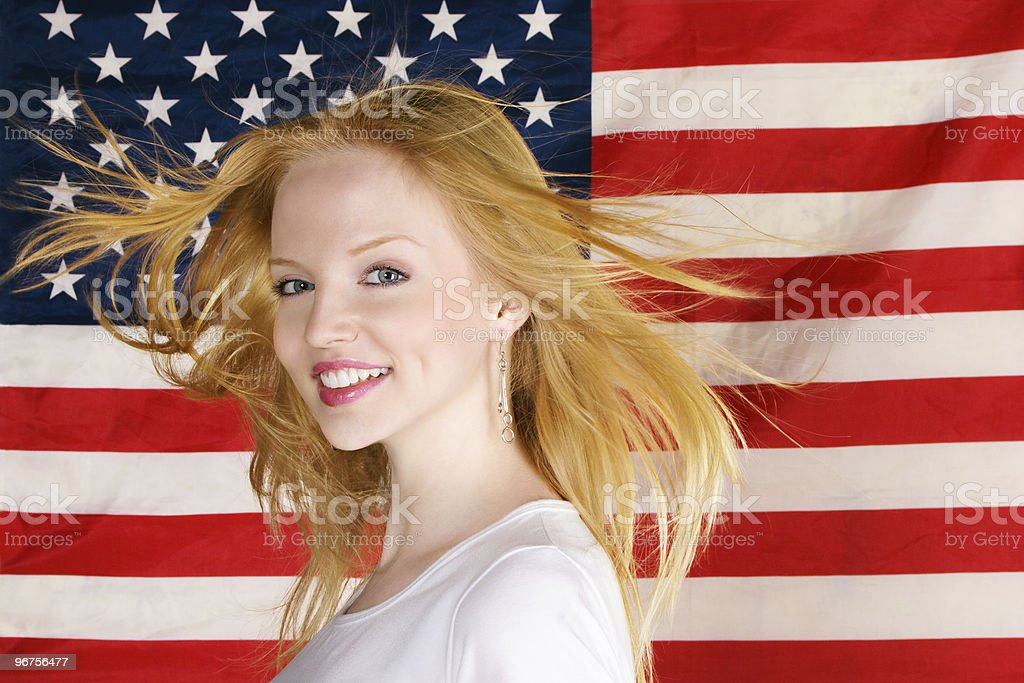 Beautiful teen girl against american flag stock photo