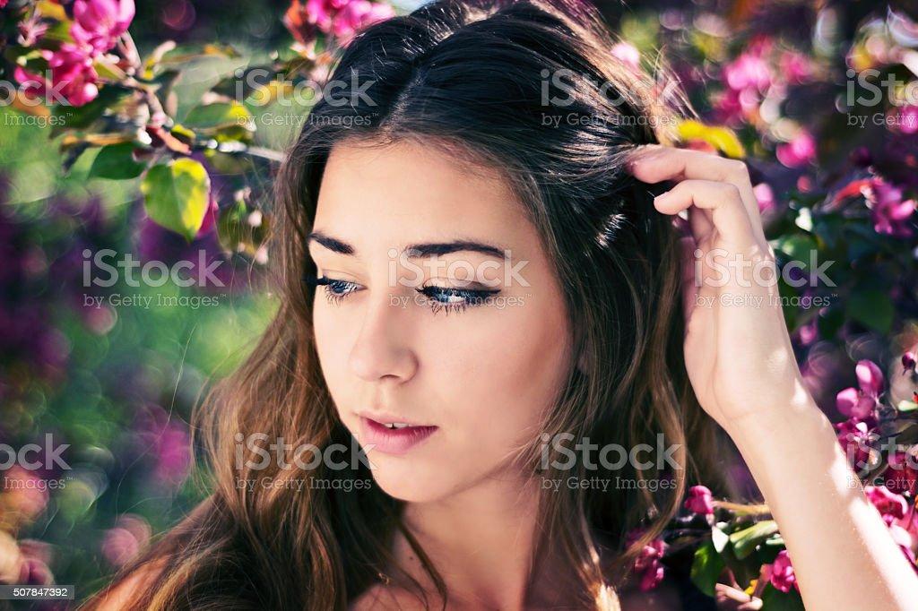 Beautiful teen girl in flowering crab apple, pulling hair back. stock photo