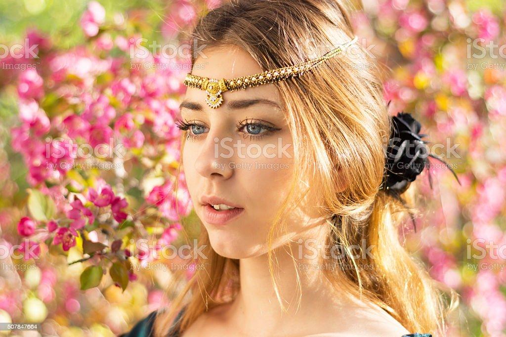 Beautiful teen girl in flowering crab apple, semi-profile stock photo