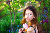 Beautiful teen girl in shady garden with pink double tulip.