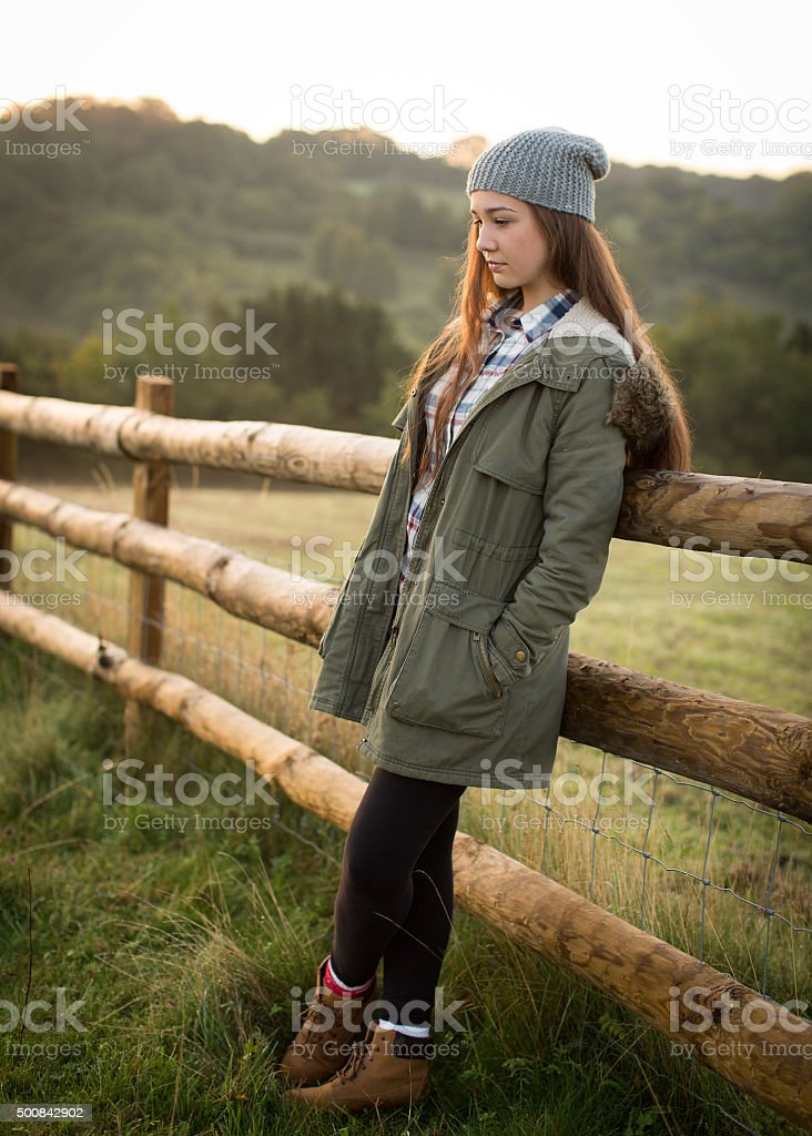 Beautiful Teen Girl Leaning Against A Farm Fence stock photo