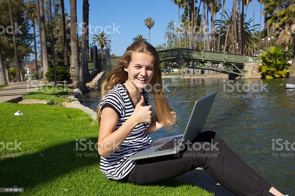 Beautiful Teen Girl on Laptop Smiles with Thumbs Up royalty-free stock photo