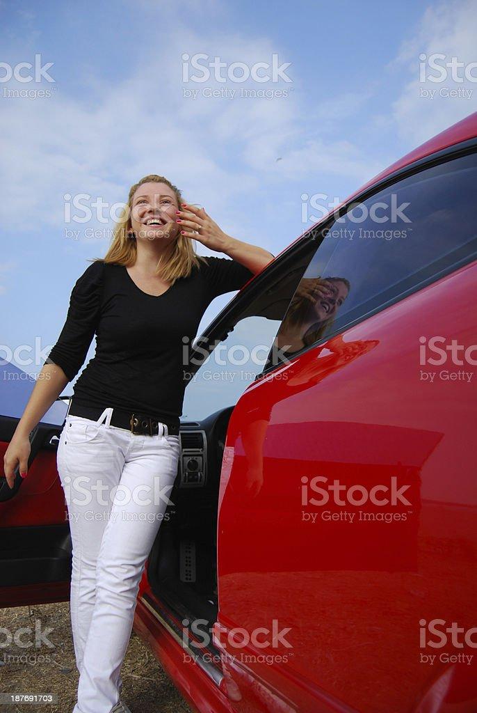 Beautiful teen girl standing by her red car door stock photo