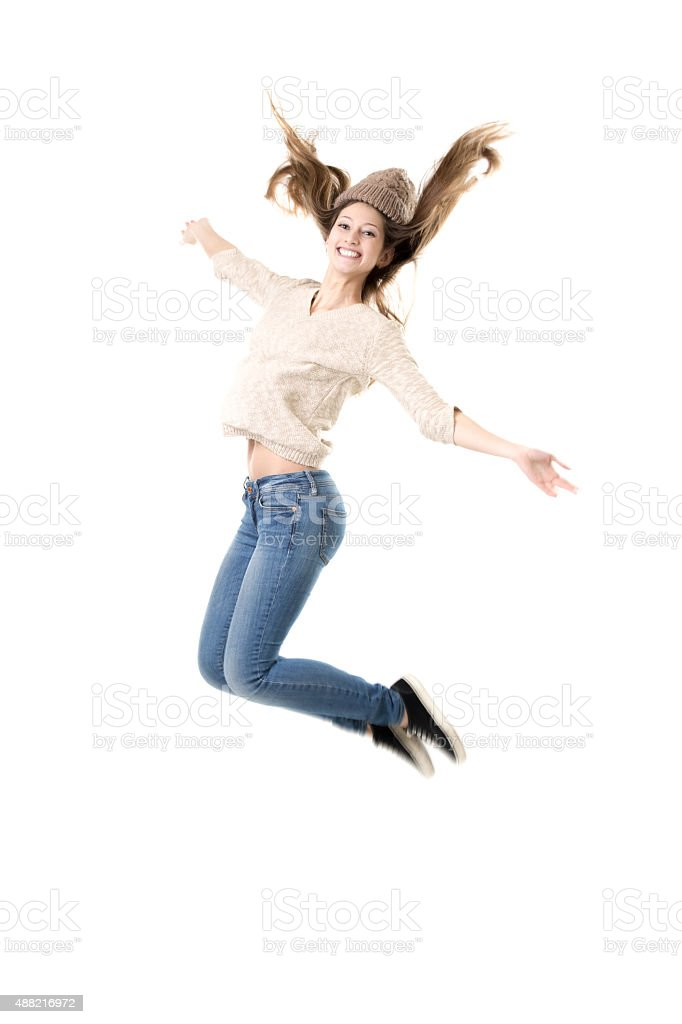 Beautiful teenage girl jumping high with delight stock photo