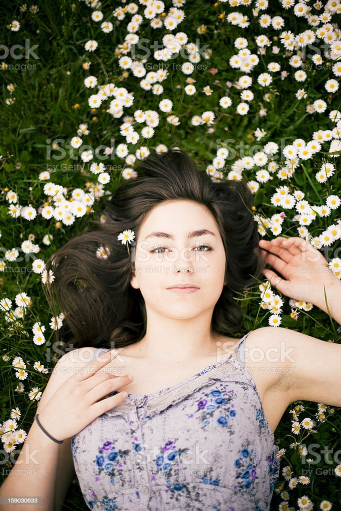 Beautiful teenage girl laying in flowers royalty-free stock photo