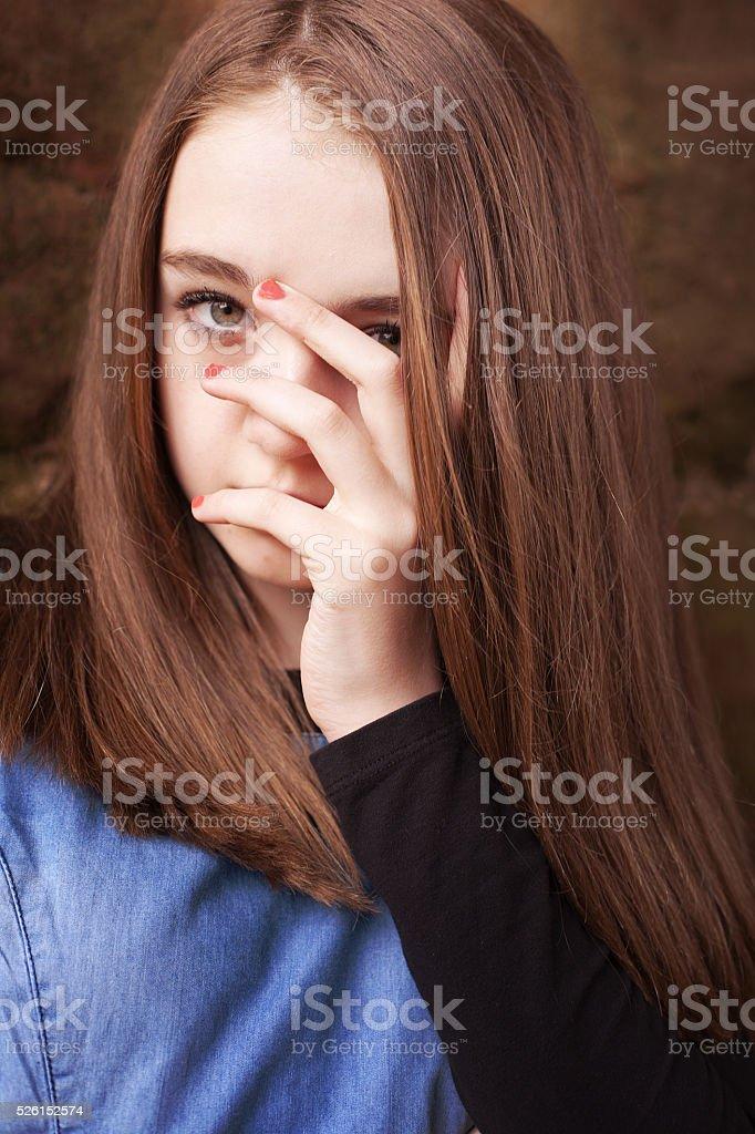 Beautiful teenage girl looking through her fingers stock photo