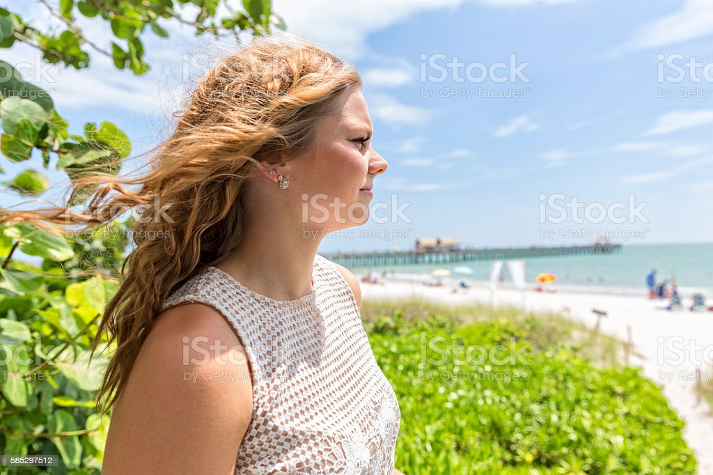 Beautiful Teenage Girl Looks Out Over the Beach in Naples stock photo