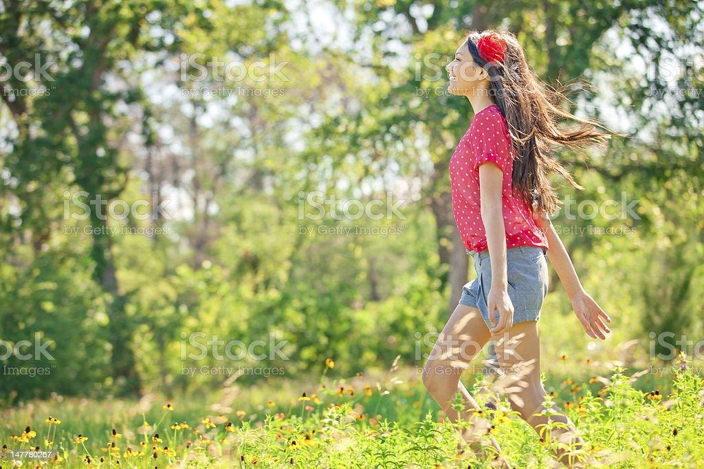 Beautiful Teenage Girl Running in Wildflower Meadow royalty-free stock photo