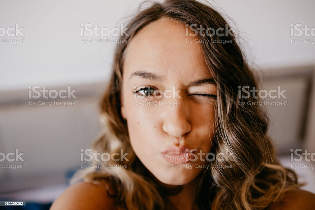Beautiful teenage girl sending kiss and winking to a camera stock photo