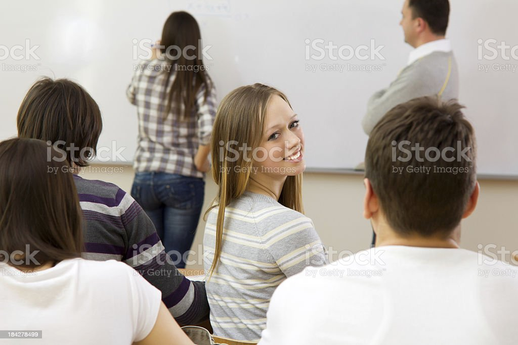 Beautiful teenage girl sitting in class, turning to camera. royalty-free stock photo