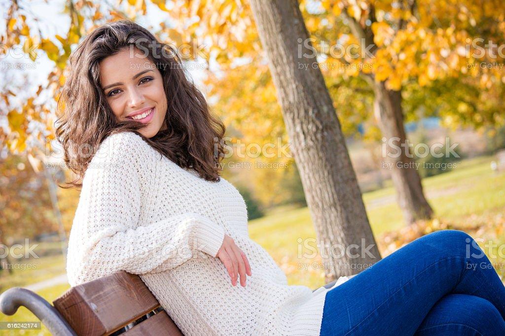Beautiful teenage girl sitting in the park stock photo