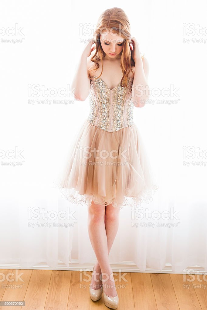Beautiful teenage girl standing against curtain stock photo