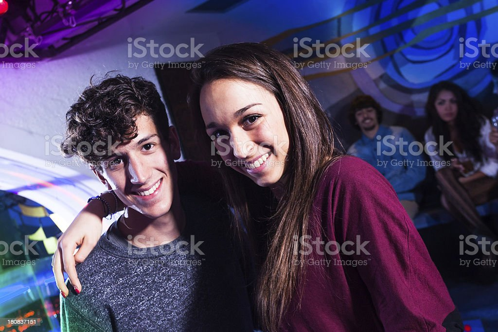 Beautiful Teenager Couple Dancing in Nightclub with Friends royalty-free stock photo