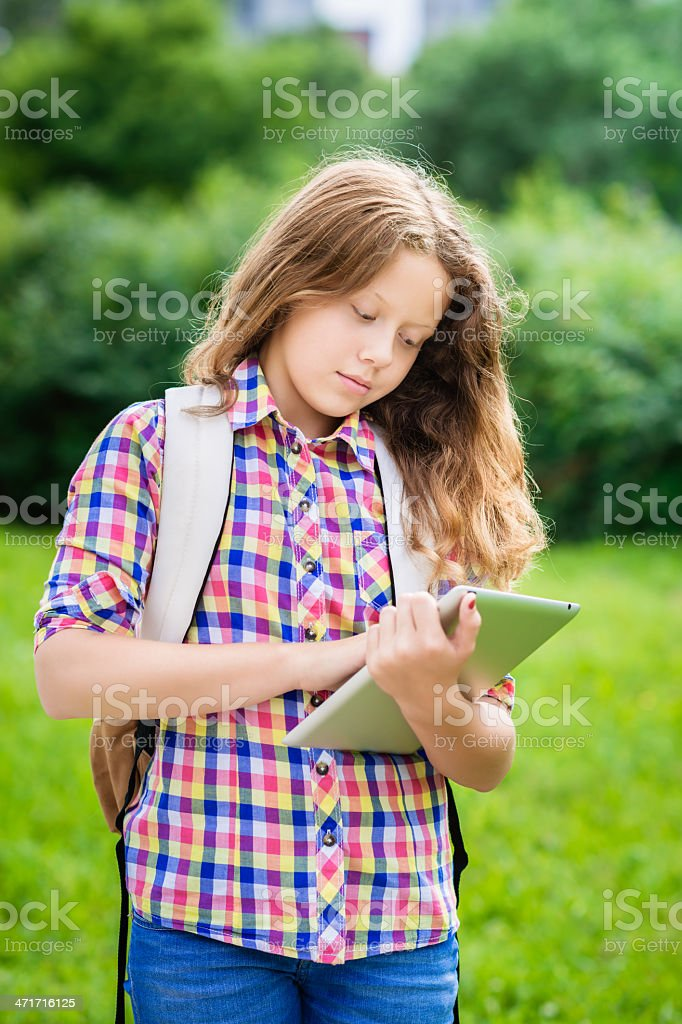 Beautiful teenager girl with backpack and digital tablet royalty-free stock photo