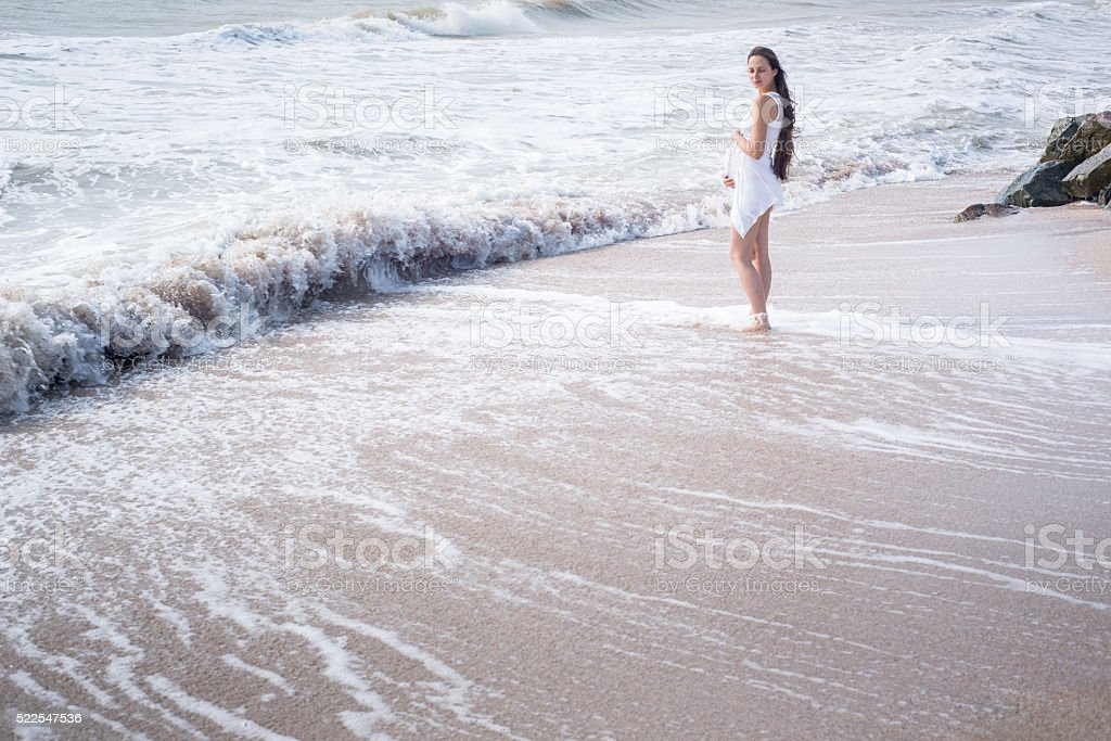 Beautiful tender pregnant woman stand on the sea shore stock photo