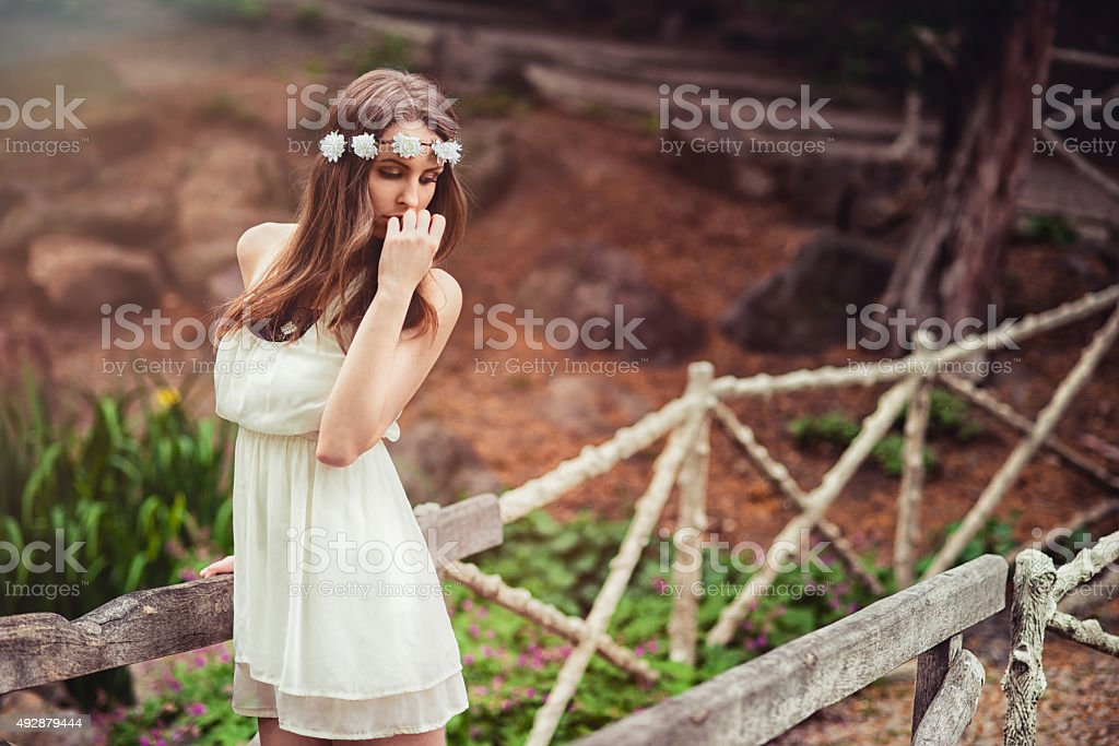 Beautiful tender woman with flower in head posing in nature stock photo