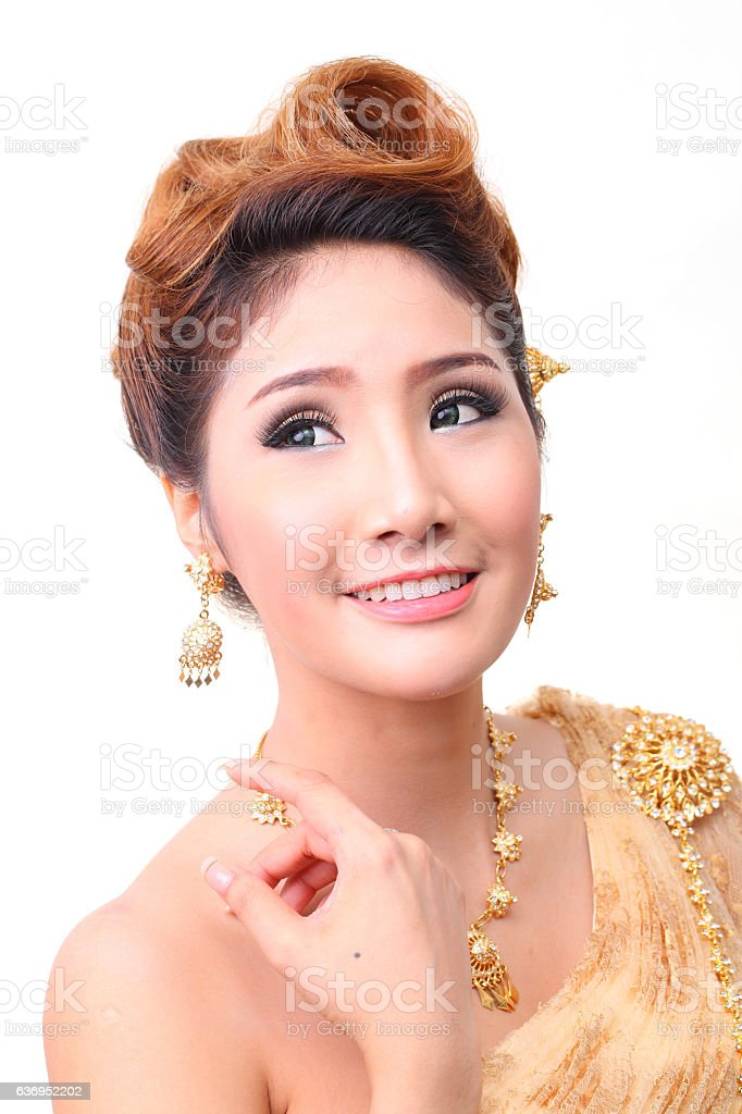 beautiful thai woman  traditional costume gold color in studio stock photo