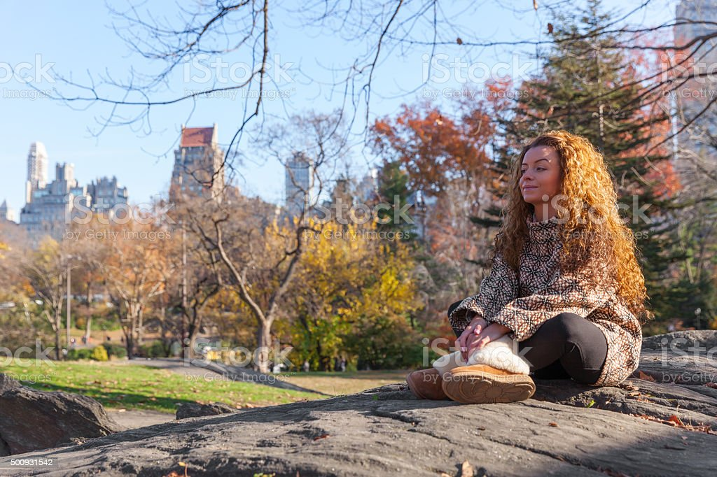 Beautiful thoughtful woman sitting cross-legged on hill top in park stock photo