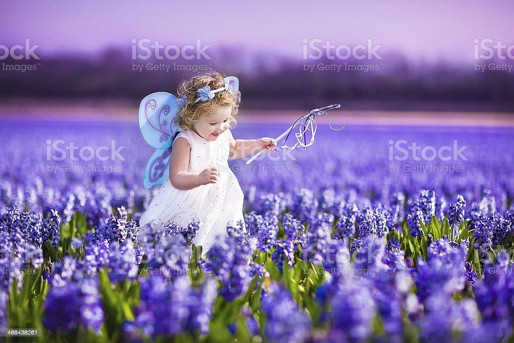 Beautiful toddler girl in fairy costume running on flower field stock photo