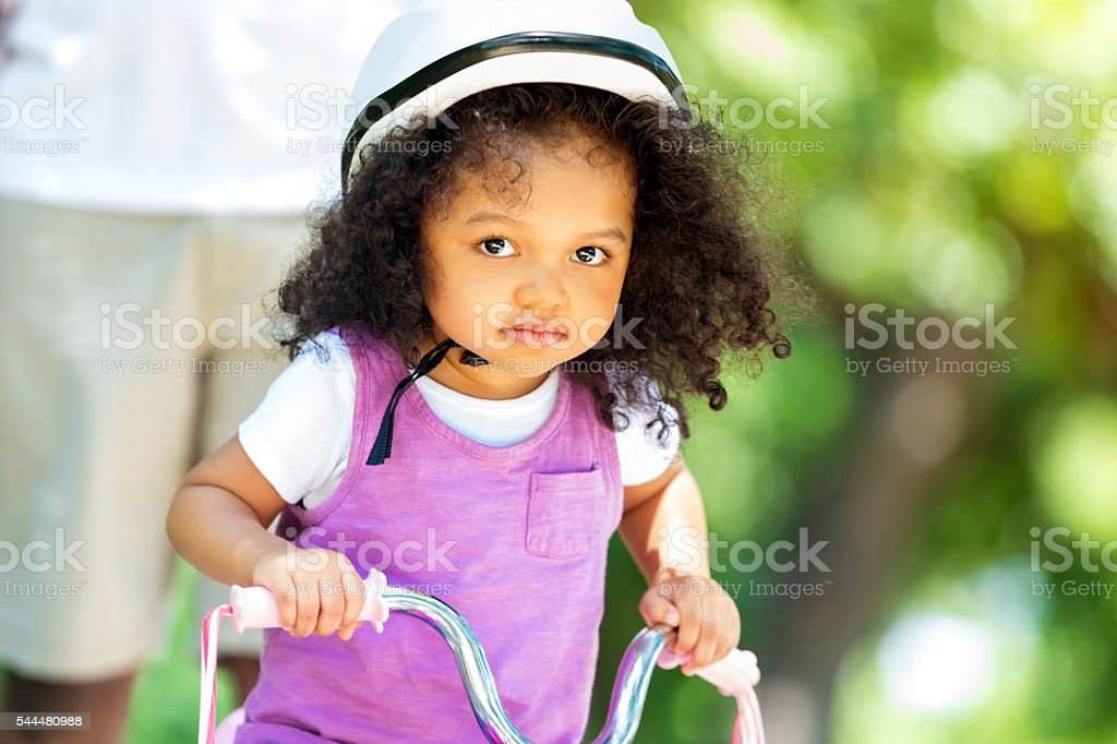 Beautiful toddler girl on a tricycle in the park stock photo