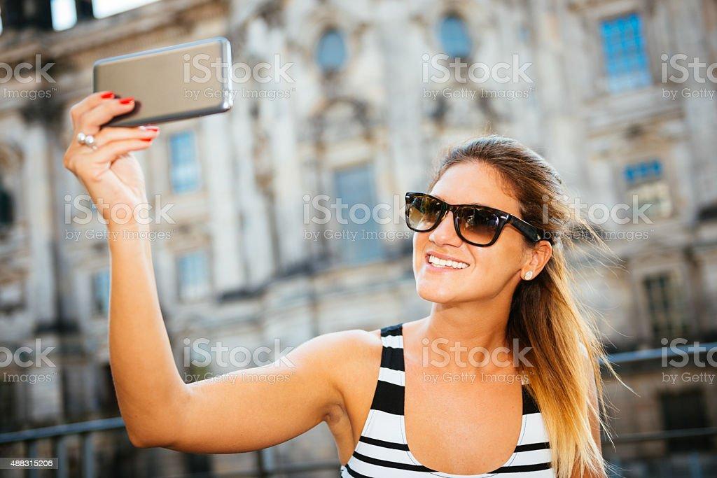 Beautiful tourist taking selfie with camera near museum in Berlin stock photo