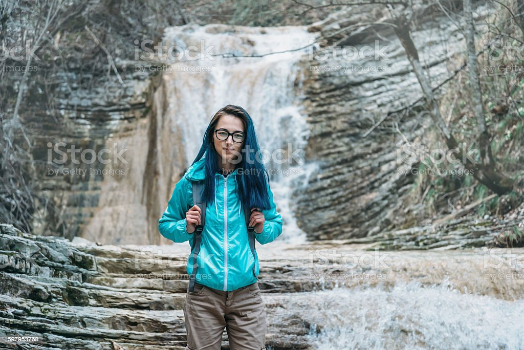 Beautiful traveler on background of waterfall stock photo