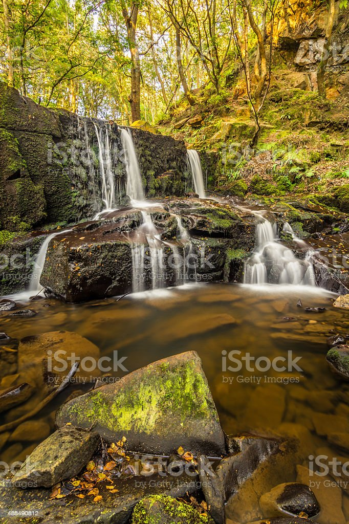 Beautiful Trickling Waterfall In Forest Woodland In Early Autumn. stock photo