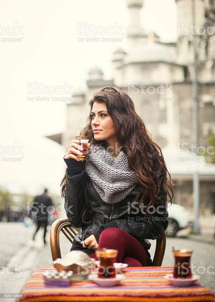 Beautiful Turkish Brunette Enjoying Tea In A Sidewalk Cafe stock photo