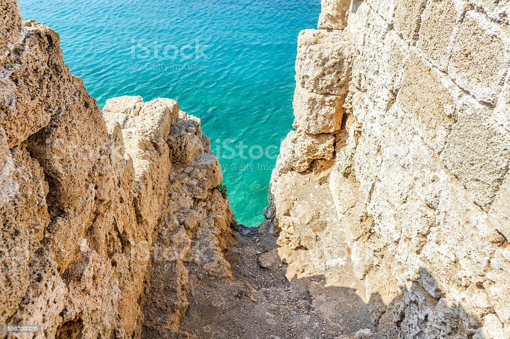 Beautiful turquoise water below castle walls in Rhodes, Greece stock photo
