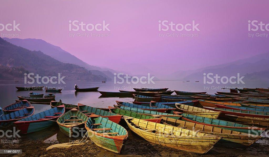 Beautiful twilight landscape with boats on Phewa lake stock photo