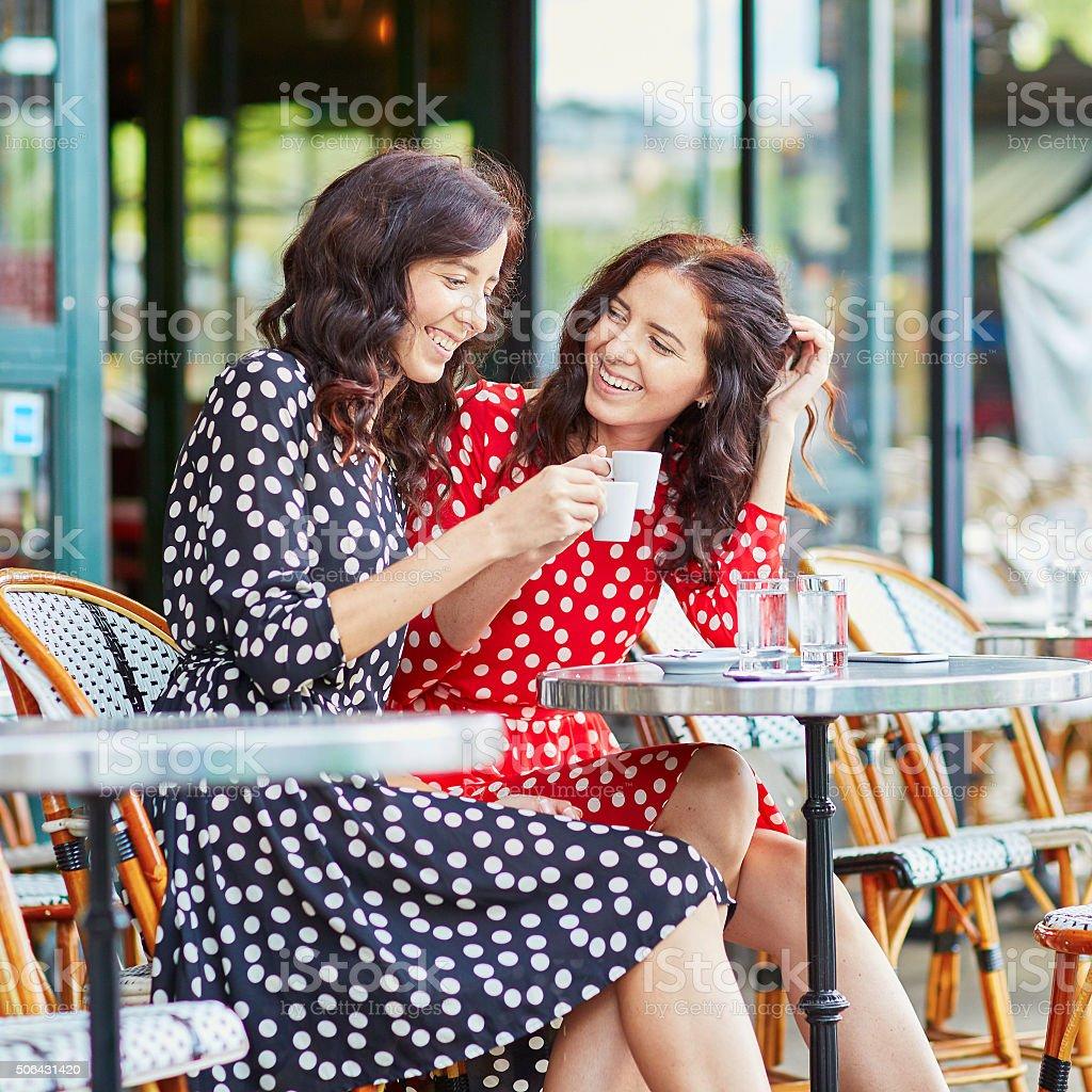 Beautiful twin sisters drinking coffee in Paris stock photo