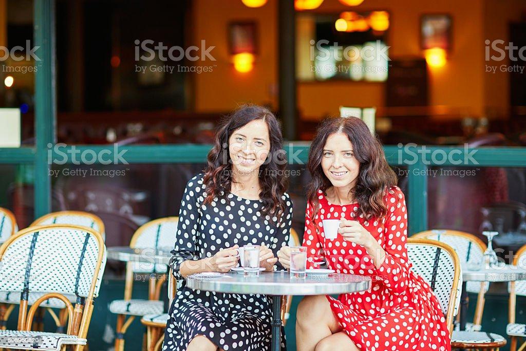 Beautiful twin sisters drinking coffee stock photo