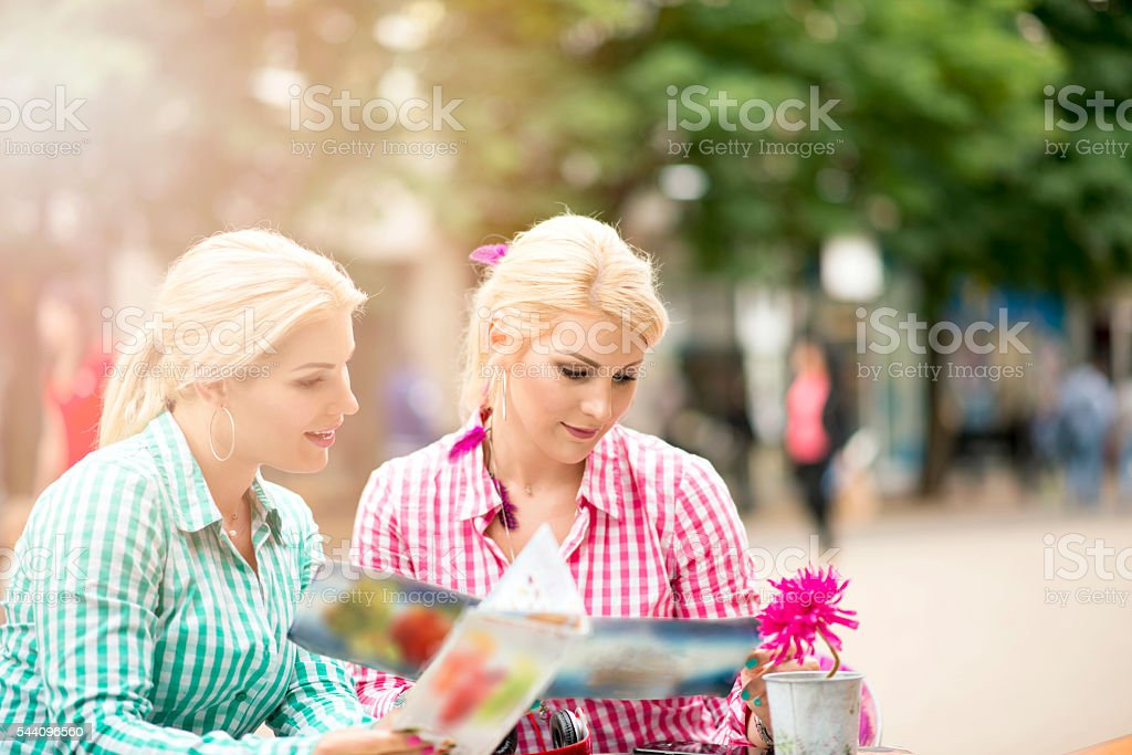 Beautiful twin sisters in a outdoor cafe stock photo