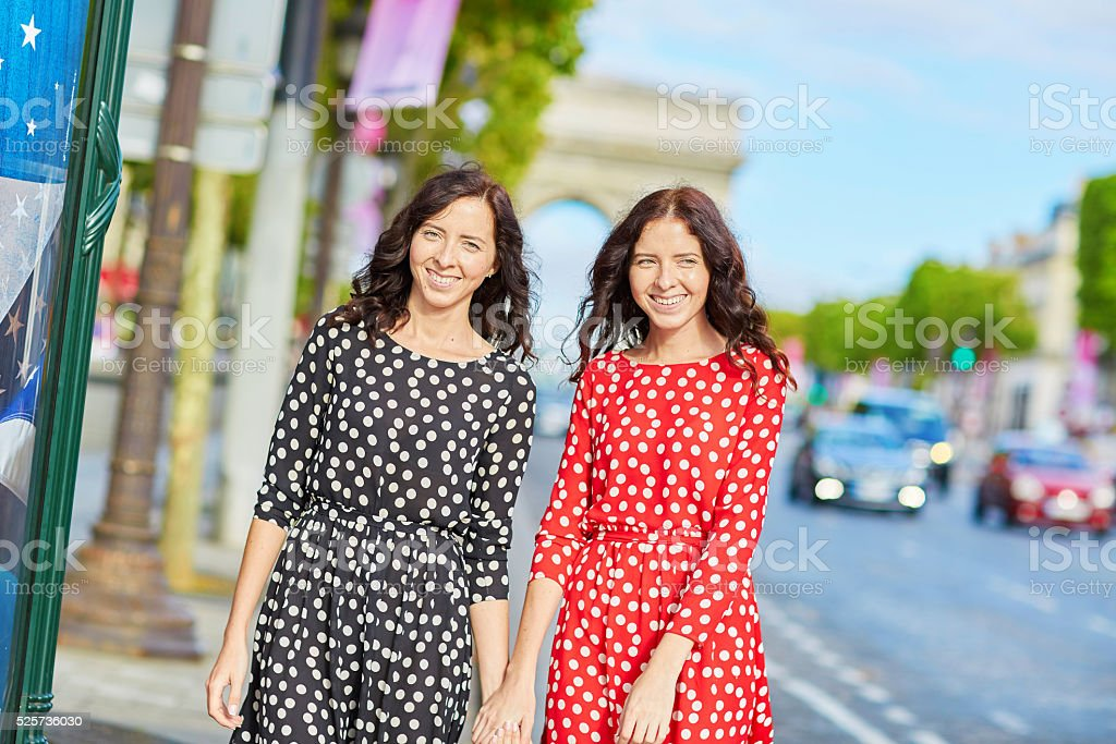 Beautiful twin sisters in front of Arc de Triomphe stock photo