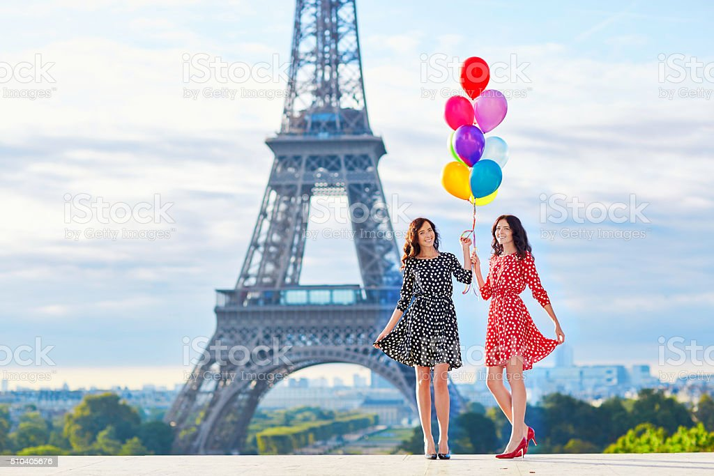 Beautiful twin sisters in front of the Eiffel tower stock photo