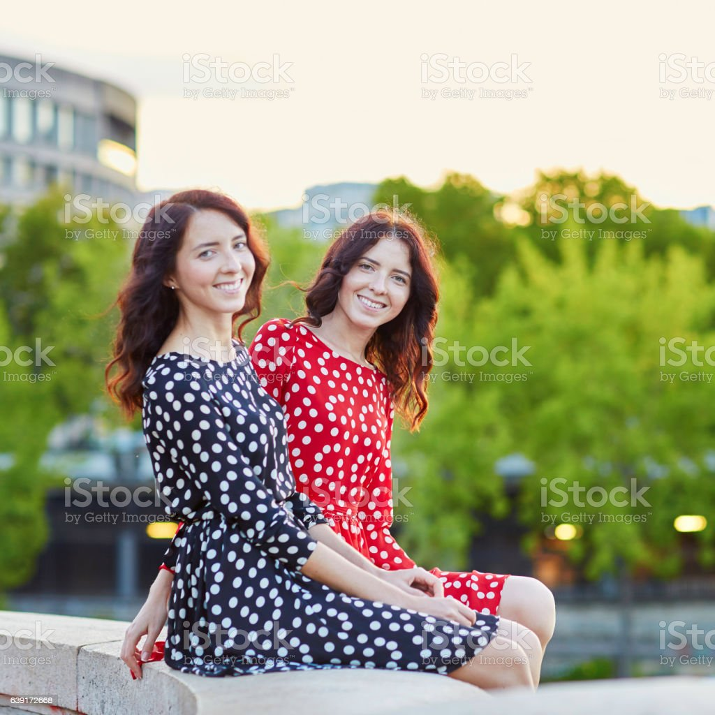 Beautiful twin sisters in red and black polka dot dresses stock photo