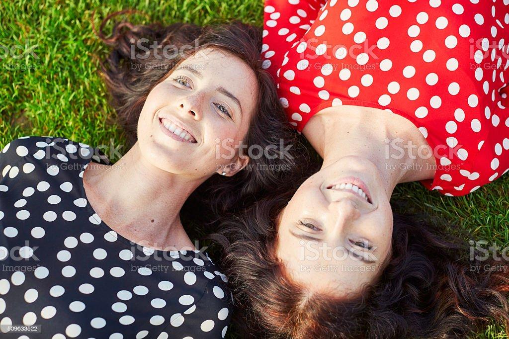 Beautiful twin sisters lying on the grass stock photo