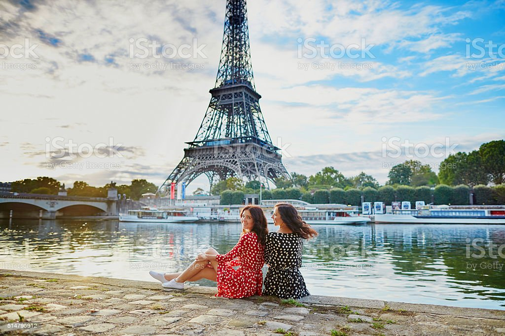 Beautiful twin sisters near the Eiffel tower in Paris, France stock photo