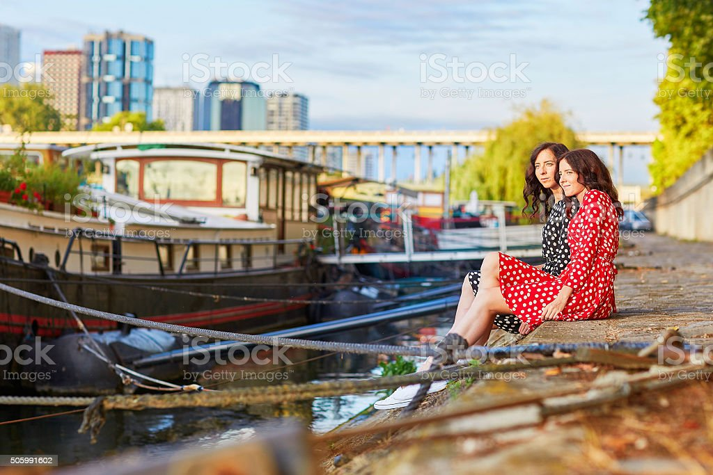 Beautiful twin sisters near the river Seine in Paris, France stock photo